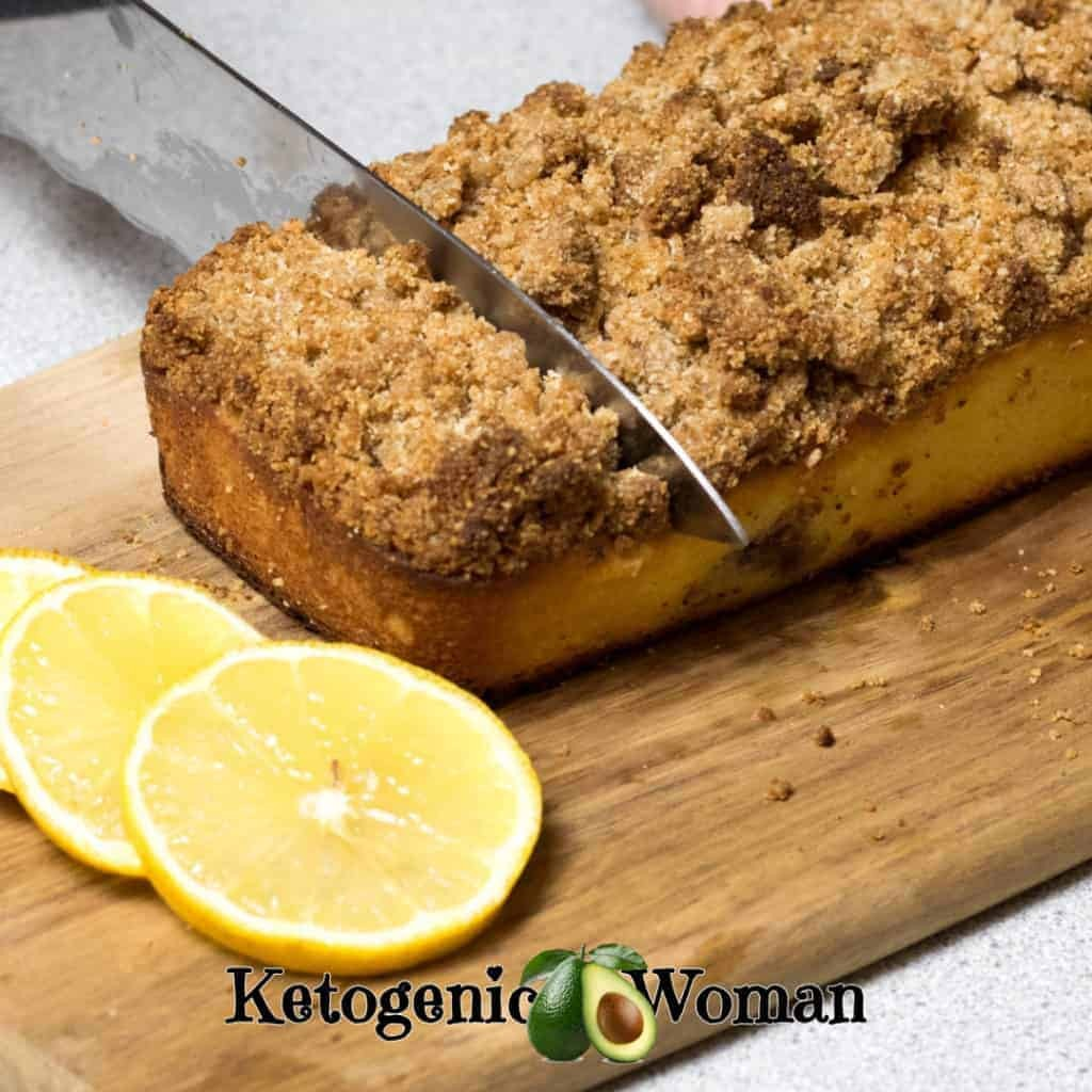 Keto Lemon Blueberry Coffee Cake on a wooden board with knife slicing through it.