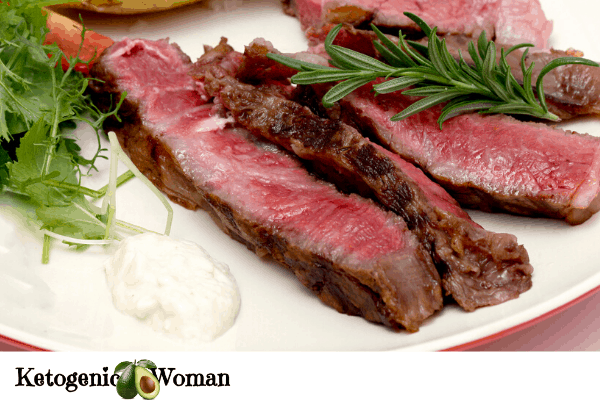Sliced roast beef with horseradish sauce and greens on a plate