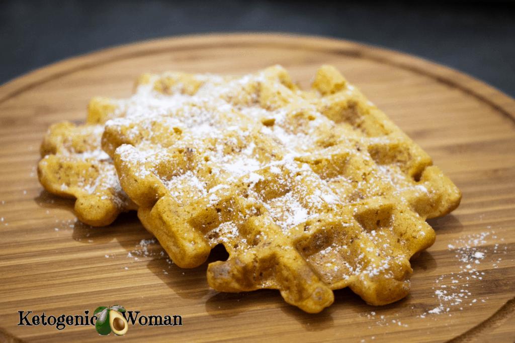 Keto pumpkin spice waffles with powdered sugar on wooden board