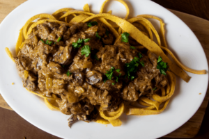 Beef Stroganoff over Noodles on White Platter