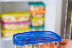 Woman taking container of food out of freezer